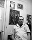Photo of Charles Bukowski posing with his art