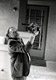 Photo of Charles Bukowski hoisting a cat skyward